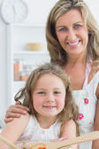 Mother hugging daughter and making salad — Stock Photo