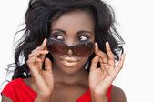 Woman tilting sunglasses — Stock Photo