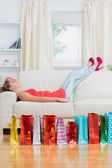 Woman relaxing on the sofa after shopping — Stock Photo