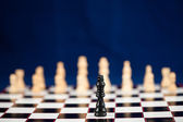 Black chess piece standing at the chessboard — Stock Photo