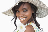 Woman smiling and holding white flower in a sun hat — Stock Photo