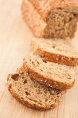 Partially sliced brown bread — Stock Photo