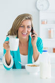 Smiling woman calling during her breakfast — Stock Photo