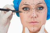 Plastic surgeon drawing on face — Stock Photo