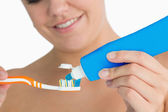Woman putting toothpaste on toothbrush — Stock Photo