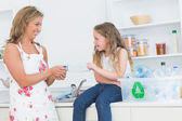 Mother sorting plastics waste with her daughter — Stock Photo