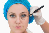 Plastic surgeon writing on woman's face — Stockfoto