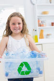 Smiling girl carrying box of the bottles — Stock Photo
