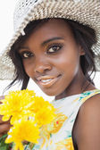 Woman wearing hat and holding flowers — Stock Photo