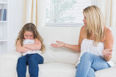 Angry mother sitting with her daughter on the sofa — Stock Photo