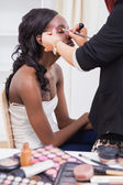 Woman sitting while getting makeup done — Stock Photo