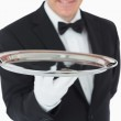 Smiling man holding a silver tray — Stock Photo