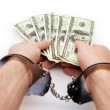 Shackled hands holding dollars — Stock Photo #23490615