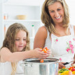 Smiling mother and daughter working at the kitchen — Stock Photo