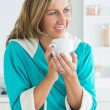 Foto Stock: Woman in dressing gown holding cup