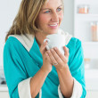 Woman in dressing gown holding cup — Stock Photo