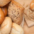 Bread in the basket with a roll on a wooden board — Stock Photo