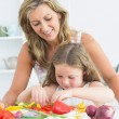 Mother teaching her daughter how to prepare vegetables — Stock Photo #23491581