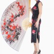 Woman in kimono standing with large silk fan — Stock Photo