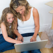 Smiling mother and daughter using laptop — Stock Photo