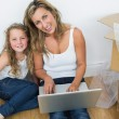 Mother and daughter sitting on the floor and using laptop — Stock Photo #23492967