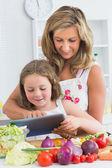 Uśmiechnięte matki i córki za pomocą tabletu — Zdjęcie stockowe