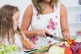 Mother cutting vegetables — Stock Photo