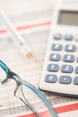 Shot of calculator and glasses — Stock Photo
