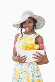 Woman with sun hat holding box with fruits — Stock Photo