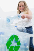 Girl throwing bottles into recycling box — Stock Photo