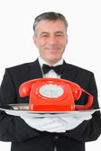 Smiling waiter holding a red phone — Stock Photo