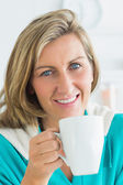 Woman holding cup with hot drink — Stock Photo