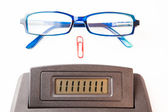 Sector of calculator display with glasses and paper clip — Stock Photo