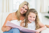 Mother and daughter sitting on the sofa with a book — Stock Photo