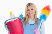 Smiling cleaner woman holding a bucket and feather duster — Stock Photo