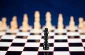One black chessman standing at the chessboard — Stock Photo