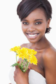 Woman smiling holding yellow flowers — Stock Photo