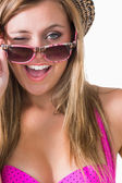 Blonde winking while holding sun glasses — Stock Photo