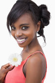 Girl in pink dress holding a flower while smiling — Stock Photo
