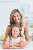 Mother hugging daughter in the kitchen — Stock Photo