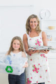Mother and daughter standing in the kitchen with waste for recyc — Stock Photo