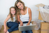 Mother and daughter sitting on the floor and using laptop — Stock Photo