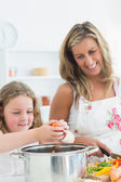 Laughing mother and daughter preparing vegetables — Stockfoto
