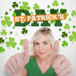 Girl in green t-shirt giving thumbs up with st patricks day greeting — Stock Photo
