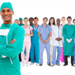 Stock Photo: Smiling surgeon with medical staff behind him