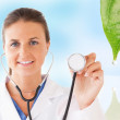 Doctor holding up stethoscope for natural treatment — Stock Photo