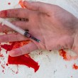 Stock Photo: Lifeless hand holding bloody syringe