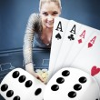 Stock Photo: Blonde womgrabbing chips with digital hand of four aces and dice