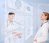 Médicos de mulheres usando interfaces futuristas — Fotografia Stock