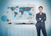 Serious businesswoman standing with a digital world map — Stock Photo